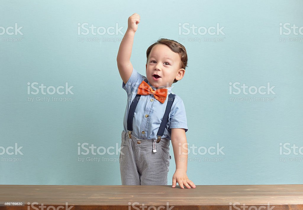 Happy and successful little boy with his hands up stock photo