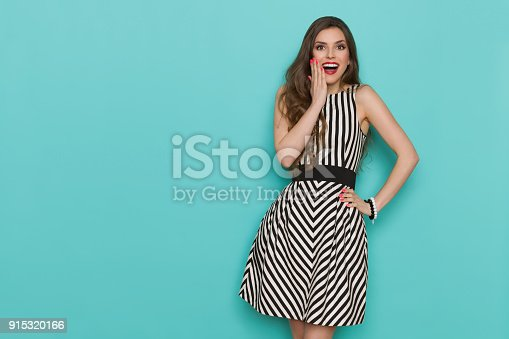 Surprised beautiful young woman in elegant black and white stroped cocktail dress is holding hand on chin, shouting and looking at camera. Three quarter length studio shot on turquoise background.