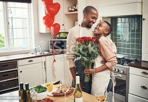 Cropped shot of an affectionate young couple posing with a bunch of flowers in their kitchen on their anniversary