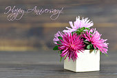 Happy Anniversary card with flowers arranged in gift box