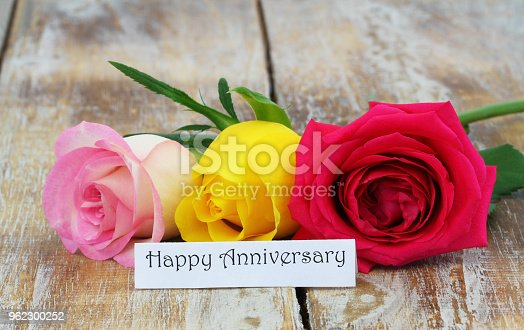 Happy Anniversary card with three colorful roses on wooden surface