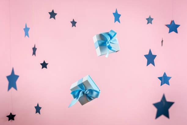 alles gute zum jubiläum! zwei kleine und blau gewickelte geschenkbox mit bändchenbogen, isoliert vor dem glanz hintergrund mit papiersterne-dekorationen - foto collage geschenk stock-fotos und bilder