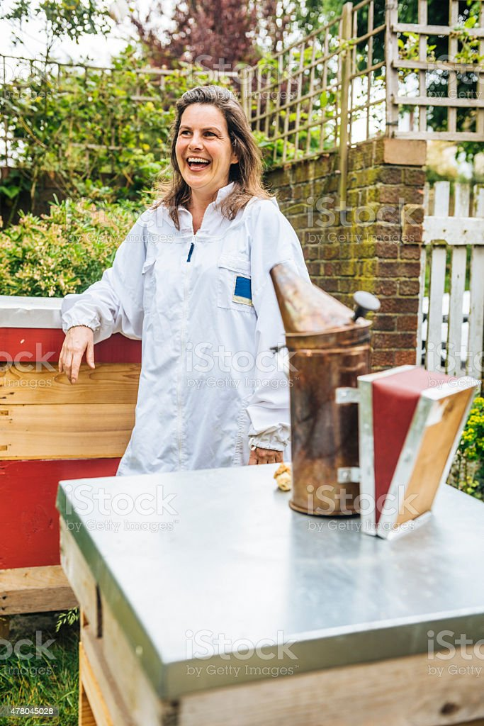 Happy apiarist with beehives stock photo
