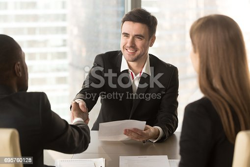 istock Happy applicant greeting employer, partners handshaking, successful deal with client 695760128
