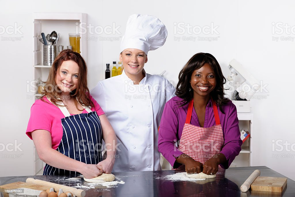 Happy Apprentices Kneading Dough In A Commercial Kitchen royalty-free stock photo