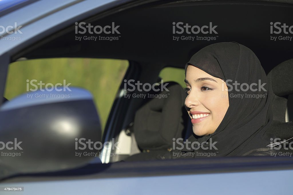 Happy arab saudi woman driving a car stock photo