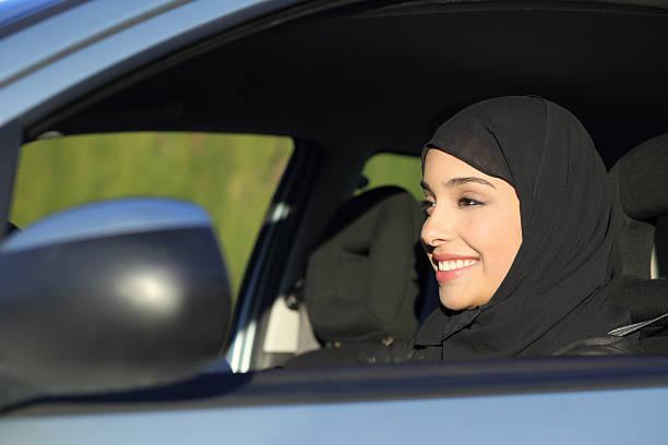 happy arab saudi woman driving a car - saudi woman stock photos and pictures