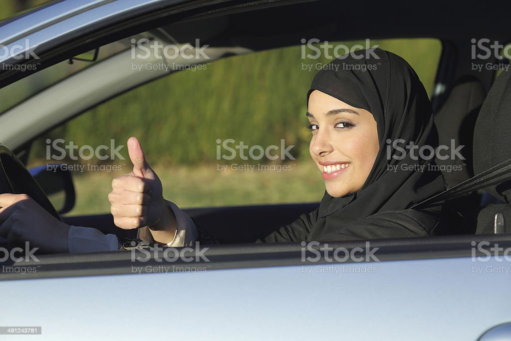Happy arab saudi woman driving a car with thumb up stock photo