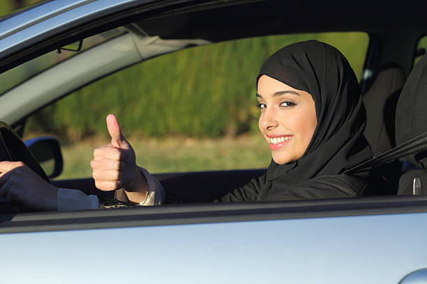 happy arab saudi woman driving a car with thumb up - saudi woman stock photos and pictures