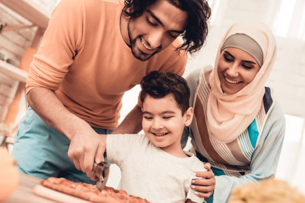 Happy Arabian Family Eating Pizza in Kitchen. Happy Arabian Family Eating Pizza in Kitchen. Muslim Family. Smiling Boy. Young Arabian Woman. Modern Kitchen at Home. Man Using Kitchenware. Young Family. Wooden Table in Kitchen. Food on Table. arabia stock pictures, royalty-free photos & images