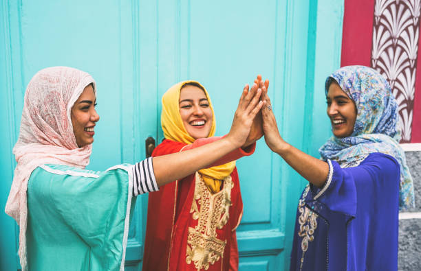 happy arabian women stacking hands together outdoor - young muslim women having fun and in the university - concept of empowering, people, religion and team work - религиозная одежда стоковые фото и изображения