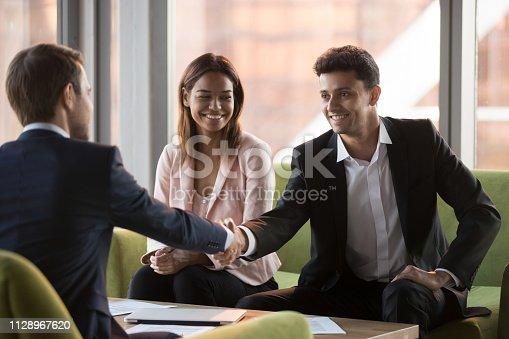 937843262 istock photo Happy arabic businessman handshaking caucasian partner at multi-ethnic meeting 1128967620