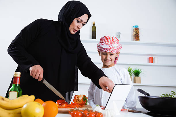 Happy Arabic child in the kitchen with his mother stock photo