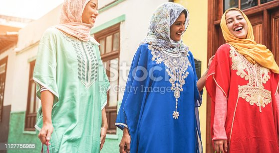 istock Happy arabic friends walking in city center - Young arabian women having fun together on sunny day - Friendship, youth, ethnic culture and religion dress concept - Focus on right girl face 1127756985