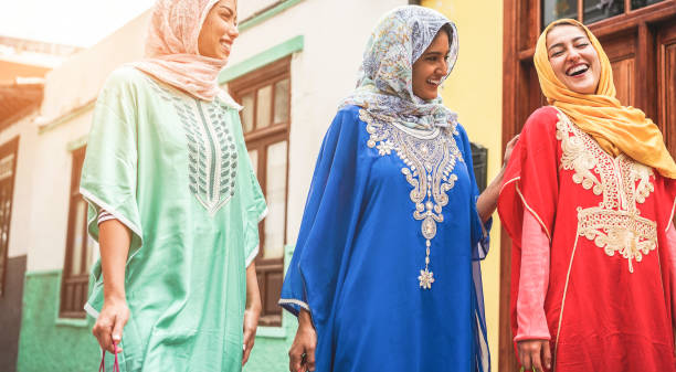 happy arabic friends walking in city center - young arabian women having fun together on sunny day - friendship, youth, ethnic culture and religion dress concept - focus on right girl face - algeria stock photos and pictures