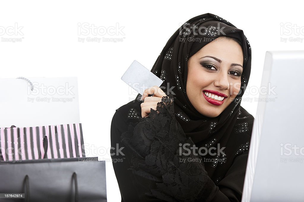 Happy Arabic girl shopping on the internet stock photo