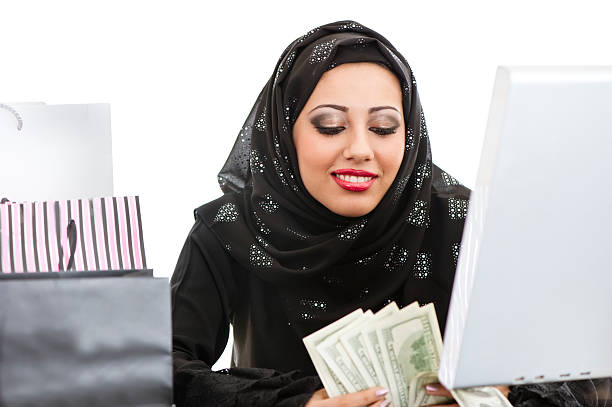 happy arabic girl shopping on the internet - kuwait currency stock photos and pictures