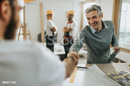 961745166istockphoto Happy architect greeting manual worker at construction site. 968827050