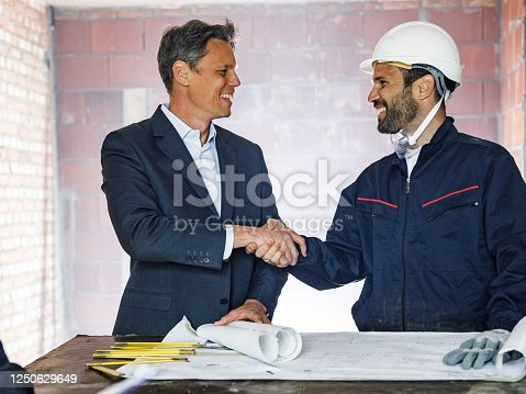 961745166 istock photo Happy architect shaking hands with manual worker at construction site. 1250629649