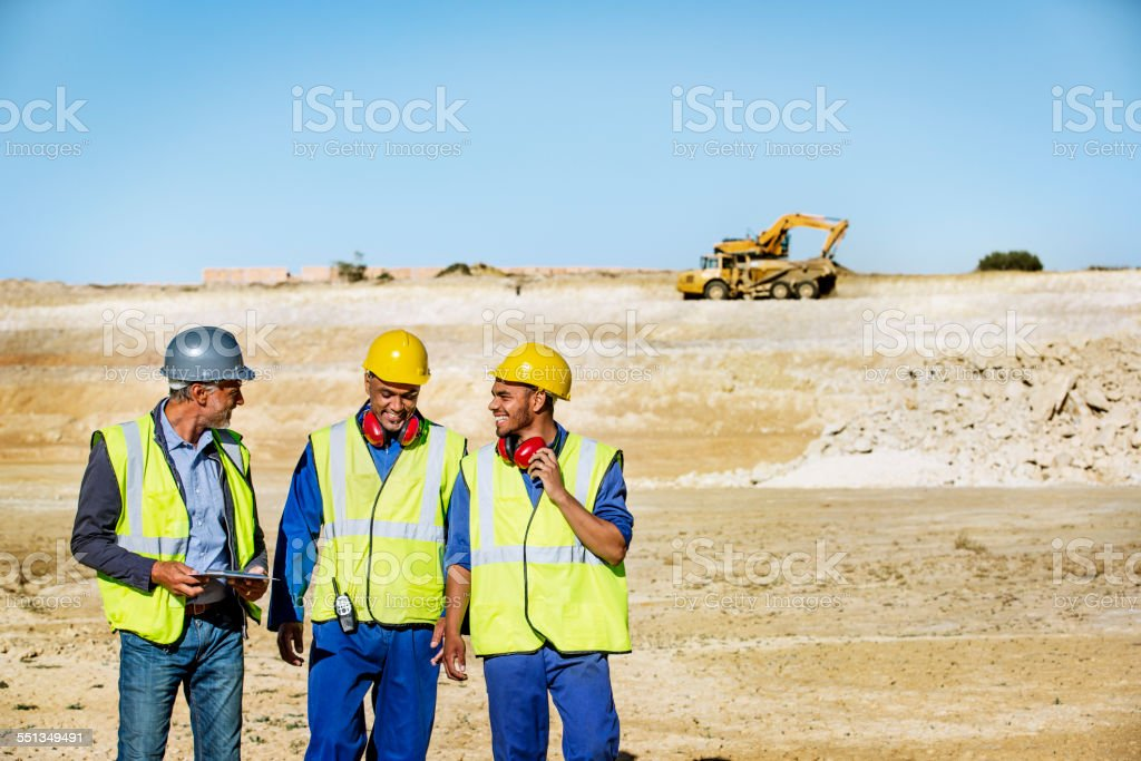 Happy architects and workers on quarry stock photo