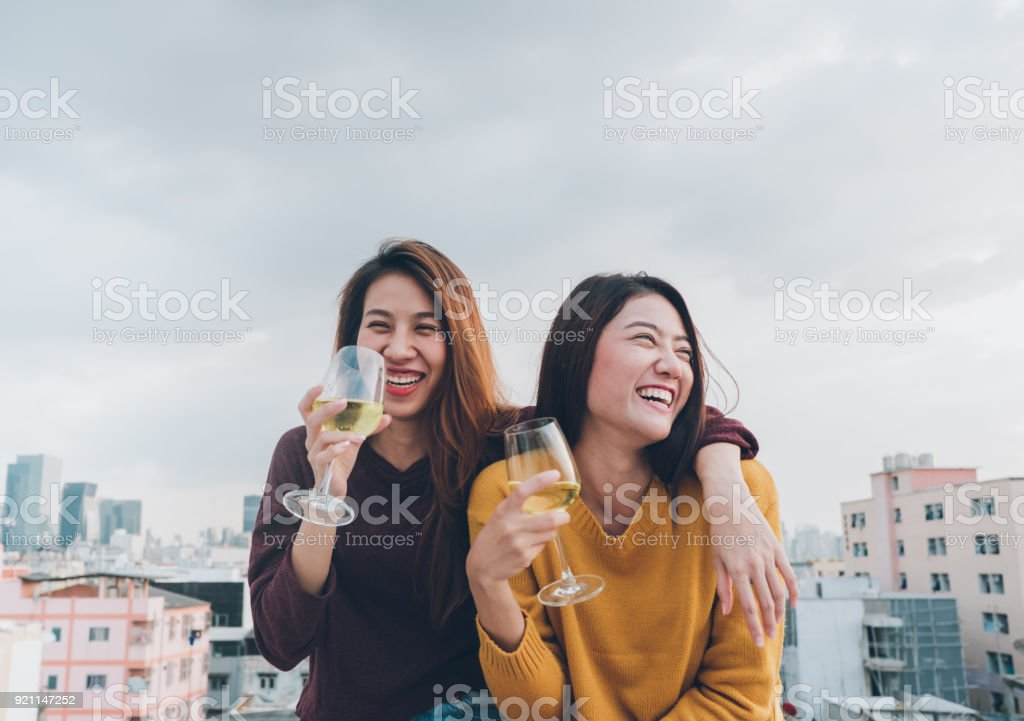 Happy asia girl friends enjoy laughing and cheerful sparkling wine glass at rooftop party,Holiday celebration festive,teeage lifestyle,freedom and fun.lesbian couple. royalty-free stock photo