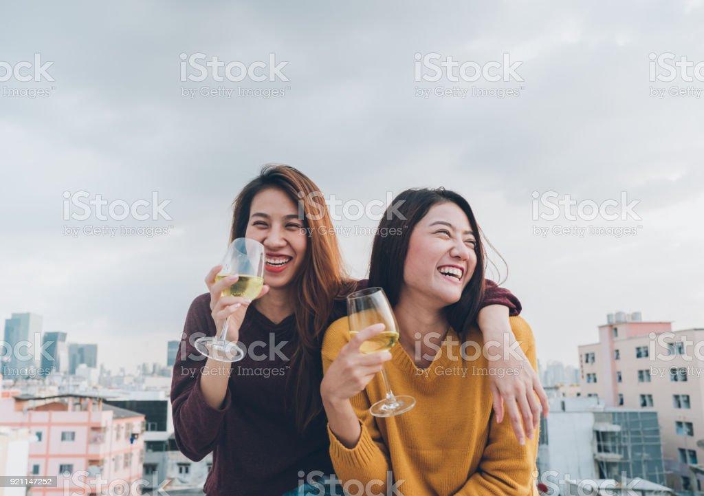 Des amis de fille Asie heureux jouissent riante et joyeuse verre de mousseux à la partie sur le toit, célébration festive de vacances, teeage mode de vie, la liberté et fun.lesbian couple. - Photo