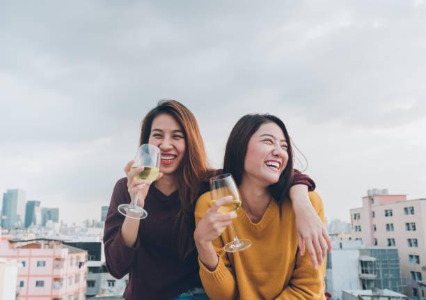 Feliz Ásia garota amigos desfrutar de copo de vinho espumante risonho e alegre festa no terraço, celebração festiva do feriado, teeage estilo de vida, liberdade e casal de fun.lesbian. - foto de acervo