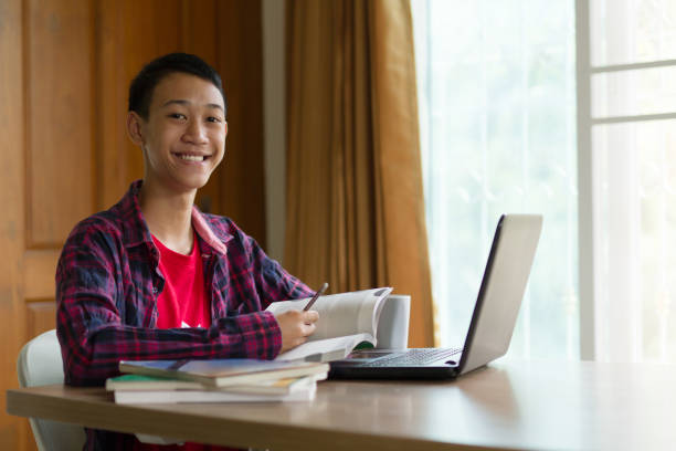 Happy asia student learning language online on laptop at home stock photo