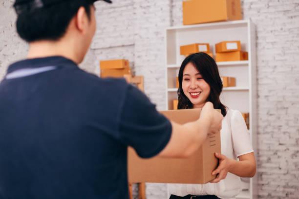 Glückliche asiatische erwachsene Business-Frau im Büro erhalten ein Paket von männlichen Zusteller – Foto