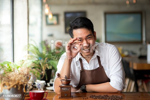 istock Happy Asian barista holding coffee beans for grinding, lifestyle concept. 1129080827