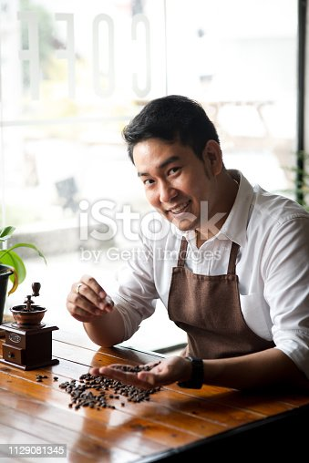 istock Happy Asian barista holding coffee beans for grinding, lifestyle concept. 1129081345