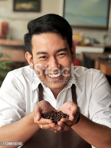 istock Happy Asian barista man holding coffee beans in his hands. 1128815743