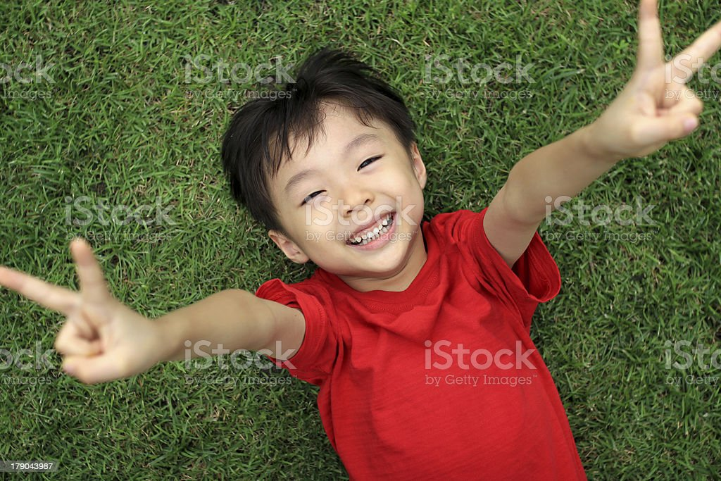 Happy Asian Boy Laying on the Grass stock photo