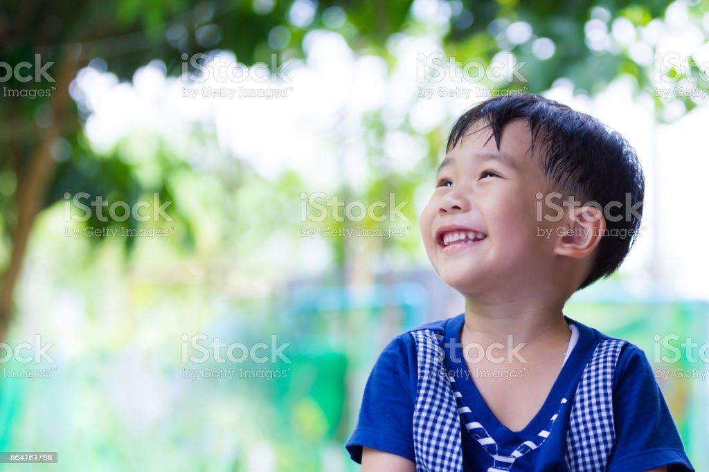 Happy asian boy looking up at park. Outdoors in the day time, travel on vacation. royalty-free stock photo
