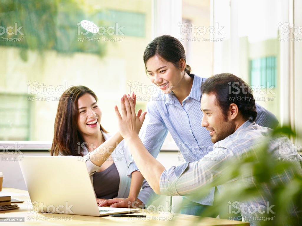 happy asian business team working together in office stock photo