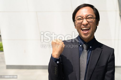 825083248istockphoto Happy Asian businessman getting good news against concrete wall outdoors 1188845158