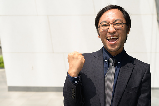 825083248 istock photo Happy Asian businessman getting good news against concrete wall outdoors 1188845158