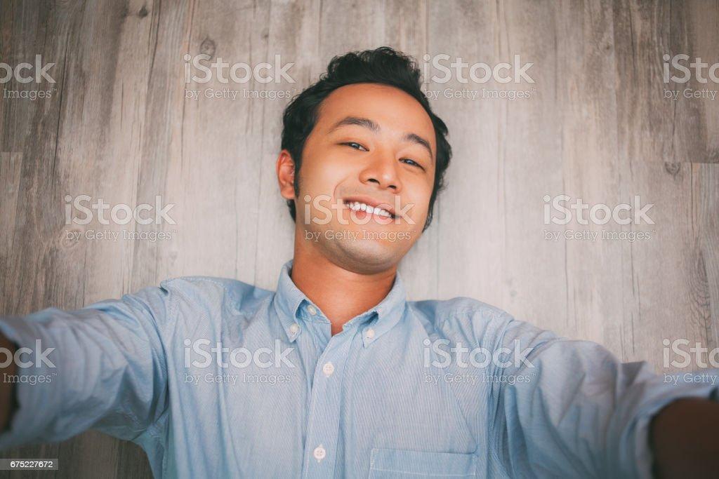 Happy Asian businessman  making selfie on floor_tone royalty-free stock photo