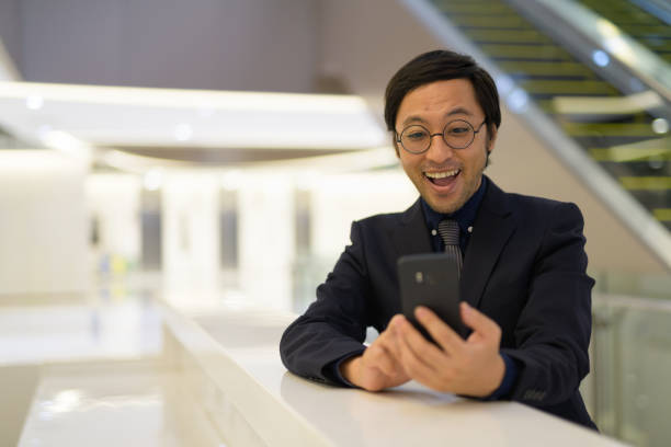 Happy Asian businessman using phone and looking shocked indoors stock photo