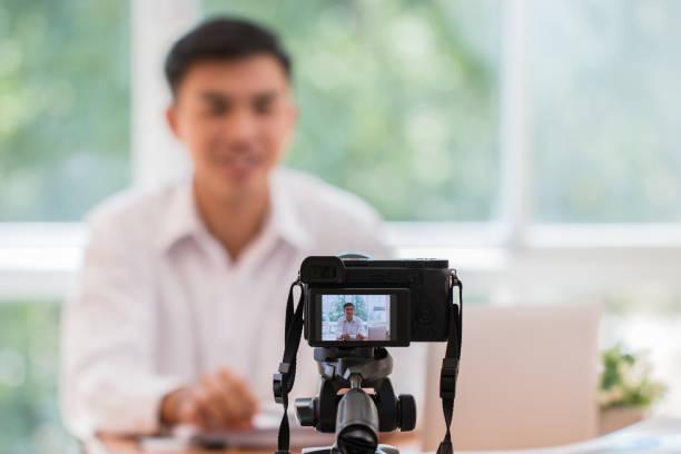 lycklig asiatisk affärs man video blogg/bloggare vlogger inspelning online-kurs eller tutorial strategi presentation passera video för undervisning live marketing dela sociala medier kanal genom mirrorless kamera - digital device classroom bildbanksfoton och bilder