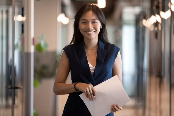 gelukkig aziatische zakenvrouw kijken naar camera stand in kantoor hal - witte boorden werker stockfoto's en -beelden