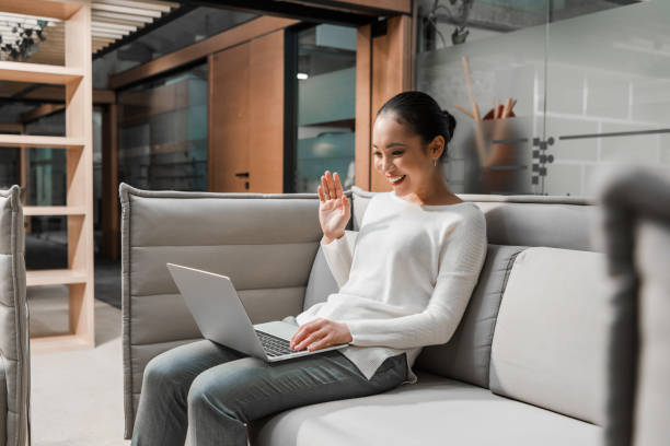 happy asian businesswoman waving hand while sitting on couch and having video chat on laptop stock photo