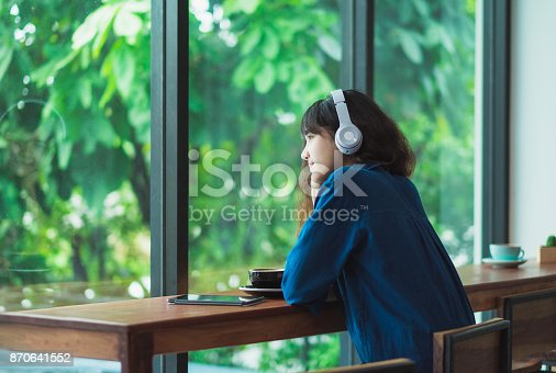 istock Happy asian casual woman listening music with headphones near window at cafe restaurant,Digital age lifestyle,chill out  life 870641552