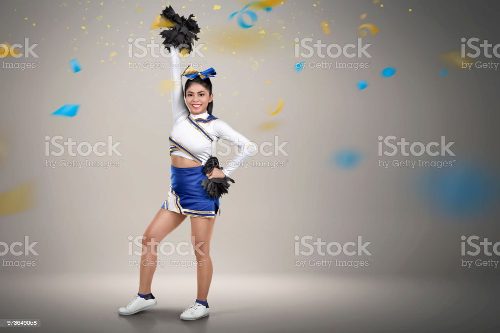 Happy asian cheerleader with pom-poms in her hands stock photo