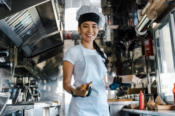 happy asian chef holding carton plates in food truck happy asian chef holding carton plates in food truck chef's whites stock pictures, royalty-free photos & images