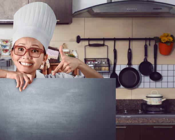 Happy asian chef showing menu sign on chalkboard – Foto