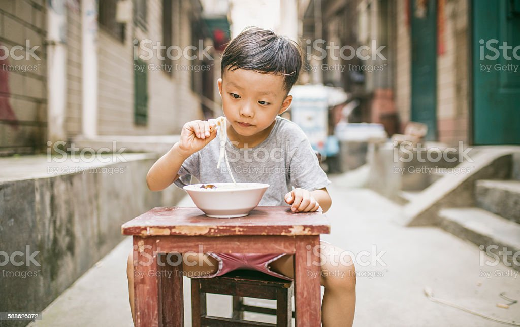 Happy Asian child eating delicious noodle with chopstick stock photo