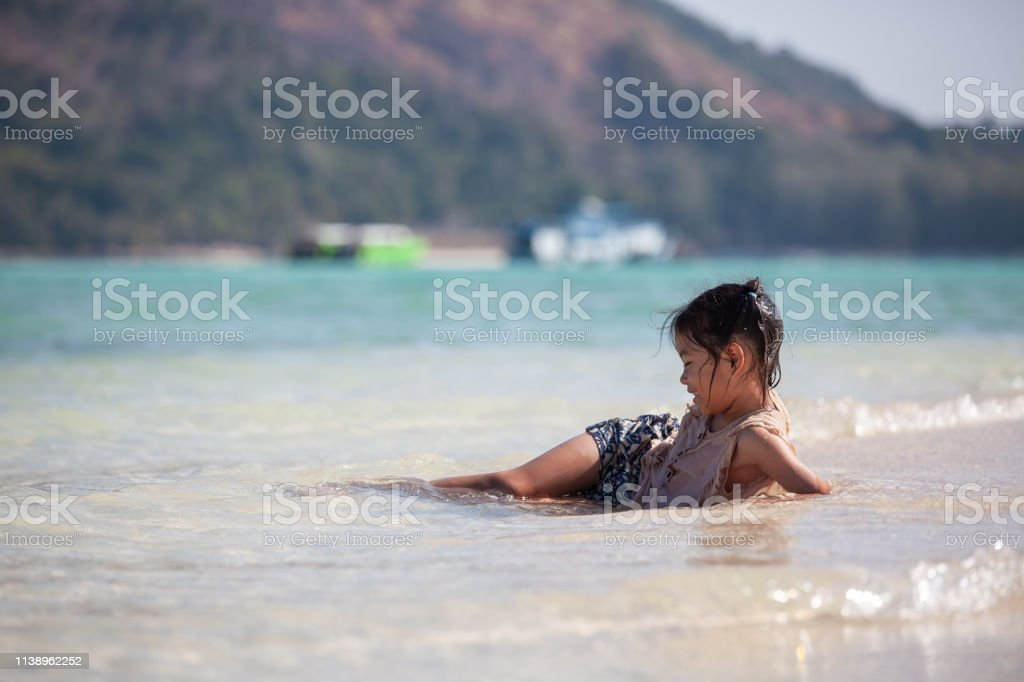 Happy asian child girl having fun to play water in the beautiful sea...