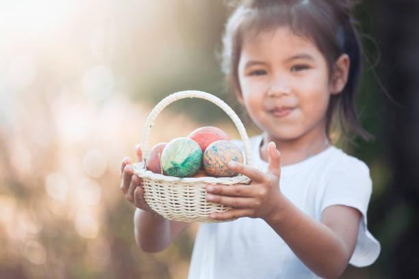 glückliches kind asiatische mädchen hält korb mit bunten ostereiern im aussenbereich - schöne osterbilder stock-fotos und bilder
