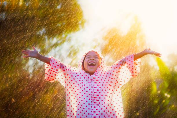 Glücklich asiatische Kind Mädchen trägt Regenmantel Spaß mit dem Regen im Sonnenlicht zu spielen – Foto